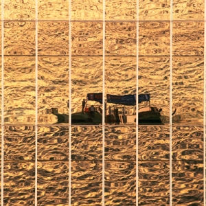 Reflection of an abra in the curved windows of National Bank of Dubai